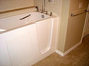 A walk-in bathtub (bathing, tub), with a door,...