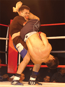 The standing fighter is attempting to escape defeat via armbar by slamming his opponent to the ground so that he will release his grip.