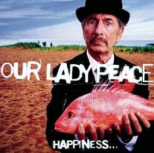 An old man standing on a sandy beach wearing a black suit and bowler derby stands holding an orange fish in both hands. He stares at the audience with a puzzled look on his face.