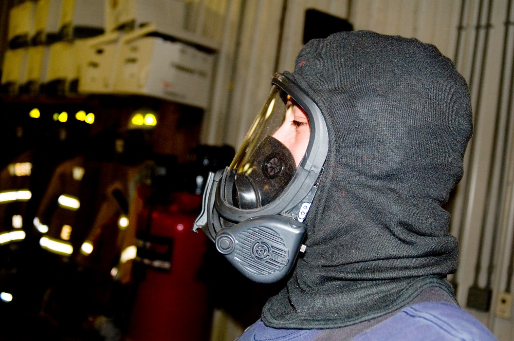 medium resolution of a person wearing an msa brand breathing mask with a nomex hood on this face piece attaches with a regulator to form a full scba