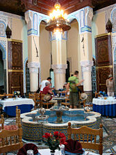 A large, open Moroccan riad that is filled with dining tables and chairs. In the center of the room is a fountain shaped like a flower with eight petals. A chandelier hangs from the ceiling, which is supported by three columns at the back. A group of people eat a meal at the table closest to the columns.