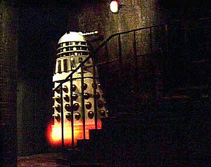 An Imperial Dalek flies up a flight of stairs ...