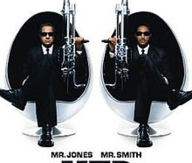 Two Men In Black Suits Sitting In Egg Shaped Chairs Holding Large Guns