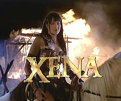 """A woman in leather armor sits on horseback with flames behind her. At the bottom of the screen in capital letters is the word """"Xena"""" in gold lettering."""