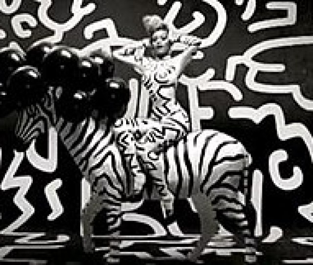 Rihanna Is Shown Wearing A Skin Tight Black And White Catsuit Sitting On A Stuffed Zebra With A Black And White Background The Scene From The Video Draws