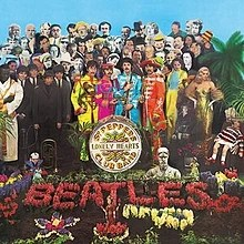 "The Beatles, holding marching band instruments and wearing colourful uniforms, stand near a grave covered with flowers that spell ""Beatles"". Standing behind the band are several dozen famous people."