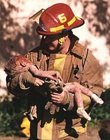 A firefighter is holding a dying toddler in his arms, and he is looking down at her. The toddler has blood on her head, arms, and legs, and is wearing white socks.