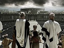 Several men in white robes are facing away from the image, at the top of large steps. A man is at the center of the image being handed flowers by a girl. In the background are rows of thousands of soldiers and members of a large crowd. In the distance, the Colosseum can be seen along with other buildings in Rome. Dark clouds are visible in the sky.