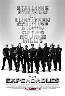 Nine armed men dressed in black standing shoulder to shoulder, Sylvester Stallone front and center.