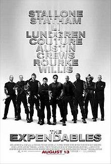 Neuf hommes armés vêtus de noir se tenant côte à côte, Sylvester Stallone devant et au centre.