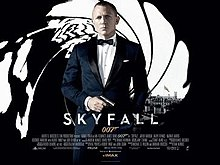The poster shows James Bond wearing a tuxedo and holding a gun, standing in front of an image that looks like it was taken from the inside of a gun barrel, with the London skyline visible behind him. Text at the bottom of the poster reveals the film title and credits.