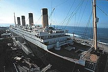 A ship resembling the Titanic is being built at a port with clear skies and small waves.