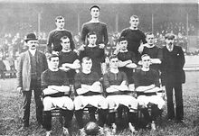A black-and-white photograph of a football team lining up before a match. Four players, wearing dark shirts, light shorts and dark socks, are seated. Four more players are standing immediately behind them, and three more are standing on a higher level on the back row. Two men in suits are standing on either side of the players.