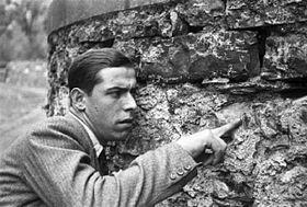 """Lazzaro indica uno dei fori di proiettile nel muro della """"Villa Belmonte"""" di Giulino dove venne fucilato Benito Mussolini."""