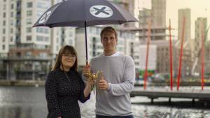 jess kelly and will brightling holding a spider award under an umbrella