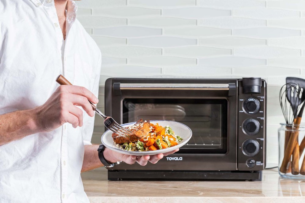 medium resolution of a man holding a cooked and plated tovala meal in front of a tovala oven