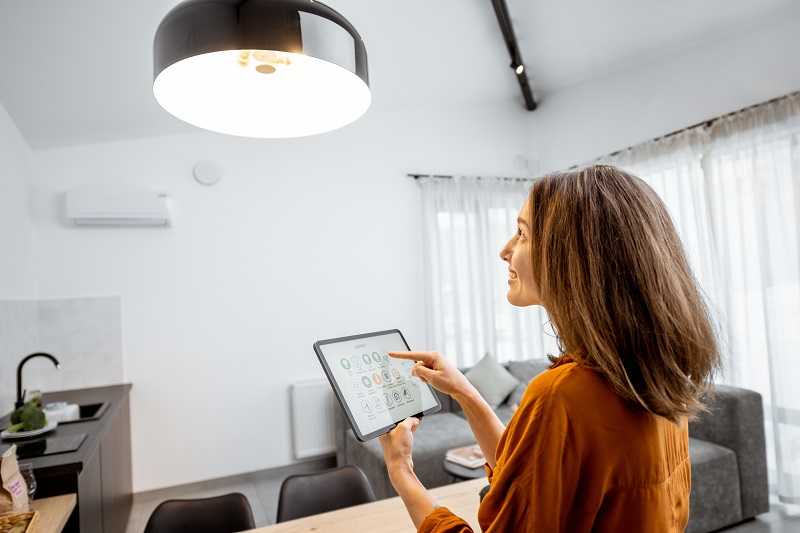 người phụ nữ sử dụng máy tính bảng để thiết lập các nhà tạo tâm trạng ánh sáng thông minh ở nhà