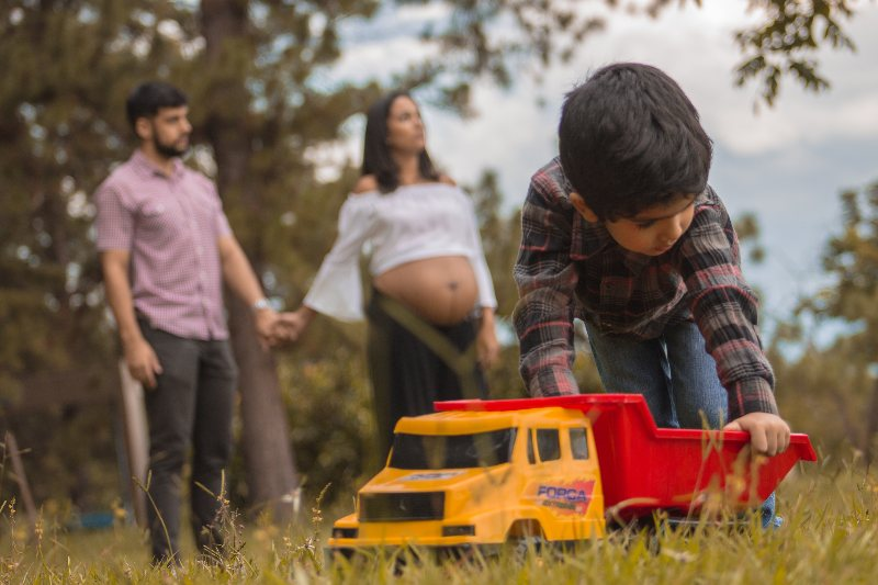 young boy playing with toy truck in field