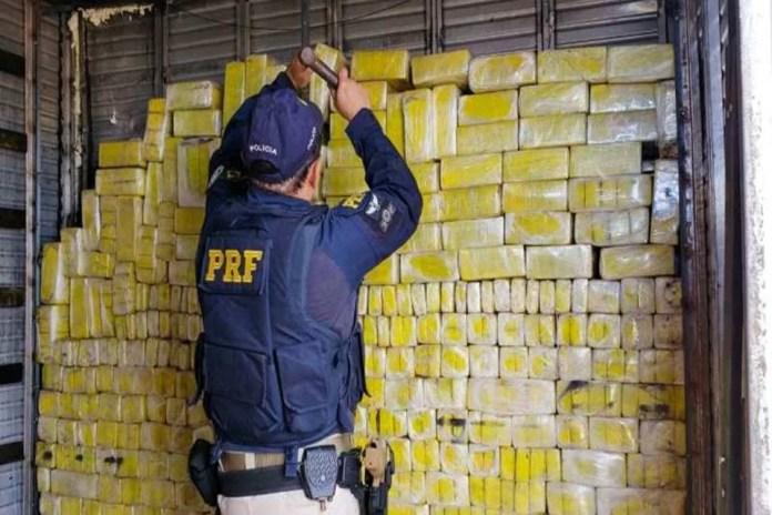 Agente com camisa da PRF manipula tablets de maconha apreendidos
