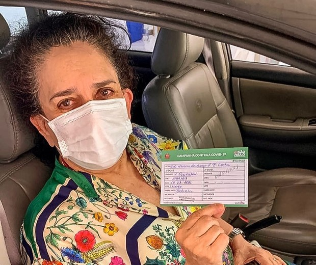 Gal Costa receiving Covid-19 vaccine, holding vaccination card