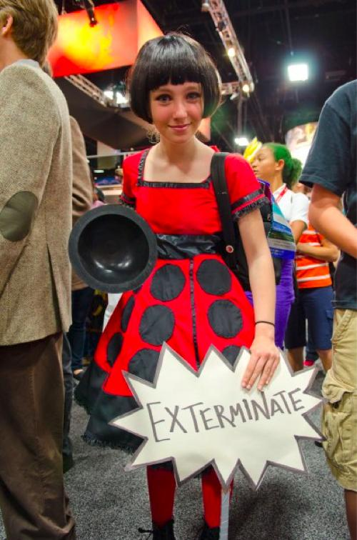 Girl wearing a dress to make her look like a dalek and holding an 'exterminate' sign