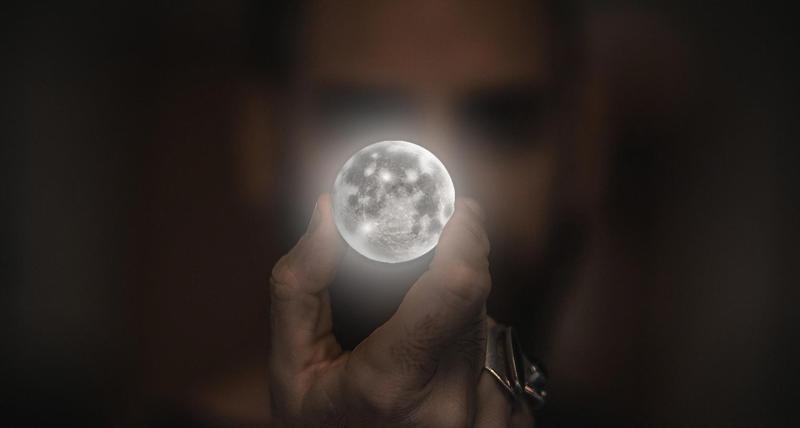 Hombre que sostiene una luna no realista