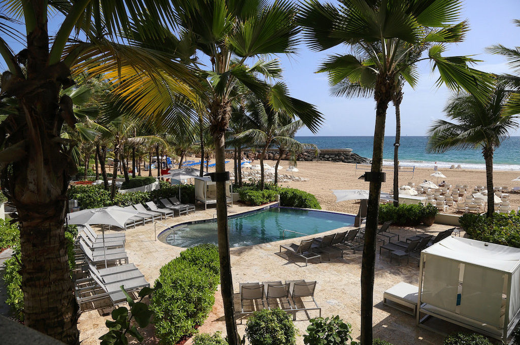 Pool and beach area of hotel with surrounding palm trees