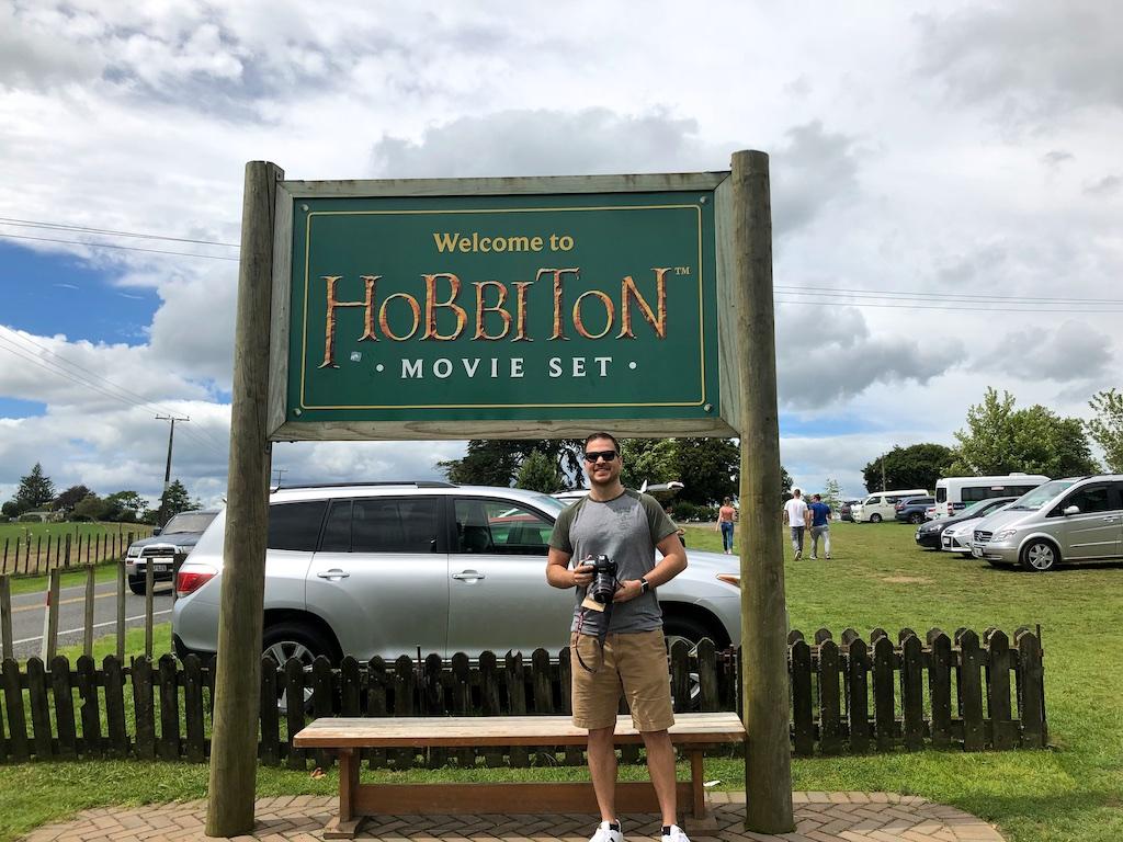 Man standing under Hobbiton movie set sign