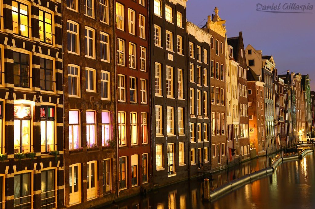 Buildings line canal in Amsterdam at night