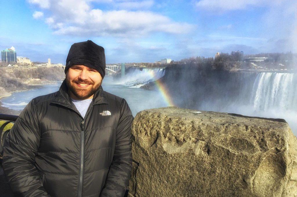 Man standing next Niagara Falls with rainbow