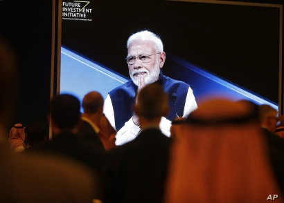 Participants watch Indian Prime Minister Narendra Modi on a screen during his speech at the Future Investment Initiative forum…