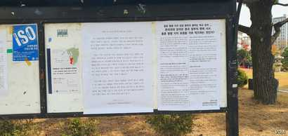 A poster announcing new school policies, and a poster opposing the school's decision. Hankuk University of Foreign Studies in Seoul on November 21, 2019. (VOA/Lee Juhyun)