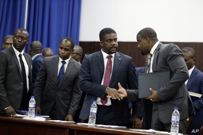 Haiti's newly appointed Prime Minister Fritz William Michel, center, talks to his advisor Wilfrid Theodore, right