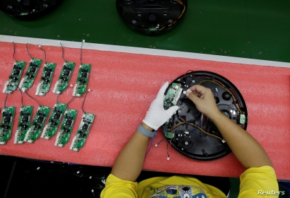 An employee works on the production line of a robot vacuum cleaner  factory of Matsutek in Shenzhen, China August 9, 2019. Picture taken August 9, 2019. REUTERS/Jason Lee