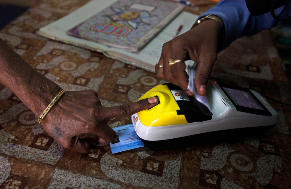 FILE-  In this March 20, 2012 file photo, an impoverished woman places her finger on a biometric card reader before buying her quota of subsidized rice from a fair price shop under the Public Distribution System in Rayagada, in Indian eastern state…
