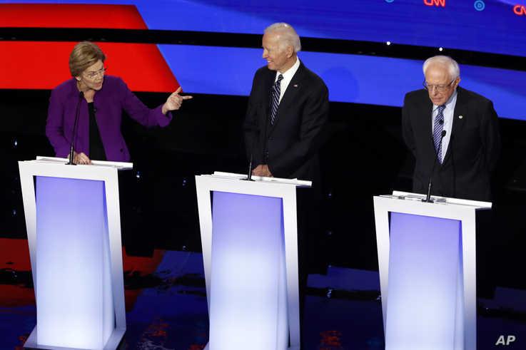 Democratic presidential candidate Sen. Elizabeth Warren, D-Mass., left, speaks to Sen. Bernie Sanders, I-Vt., right as former…
