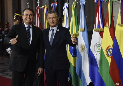 FILE - Argentina's President Mauricio Macri, right, gives a thumbs up to photographers with Brazil's President Jair Bolsonaro during the Mercosur Summit in Santa Fe, Argentina, July 17, 2019.