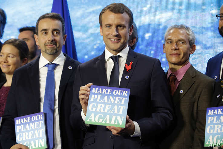 French President Emmanuel Macron holds a sign with the slogan 'Make our planet great again' as he attends the 'Tech for Planet'…