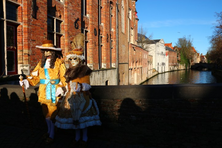 A couple wearing venetian masks and costumes in Bruges