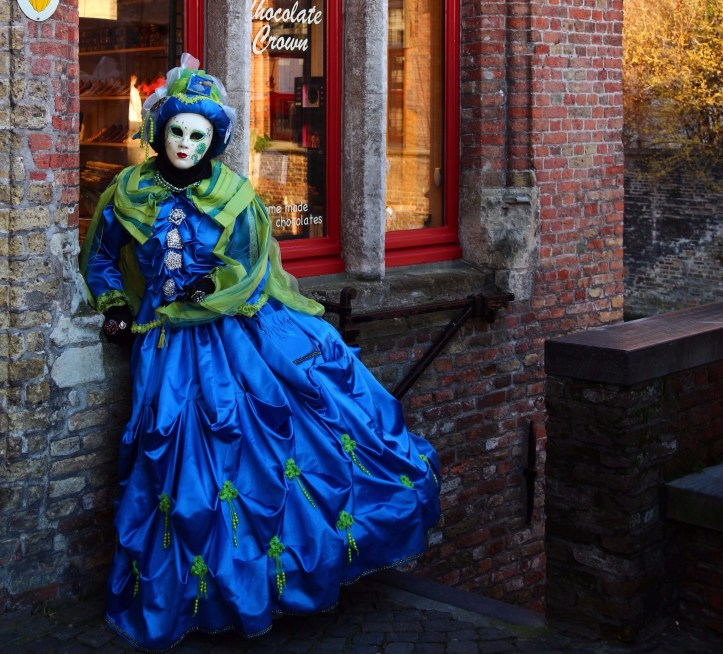 Venetian costumes in Bruges. A masked performer wearing a blue venetian costume is posing in Bruges