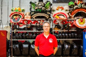 Billy Greer, standing in front of traditional Chinese Lion costumes.