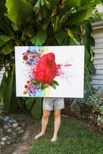 """Artist Stephanie Claire Baker with her exploding strawberry acrylic painting titled """"Absolutely none of it"""" Photo by Mary Ella Jourdak"""