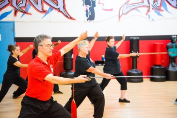 Participants in a Tai Chi class utilizing movements with weapons, Billy Greer leads.