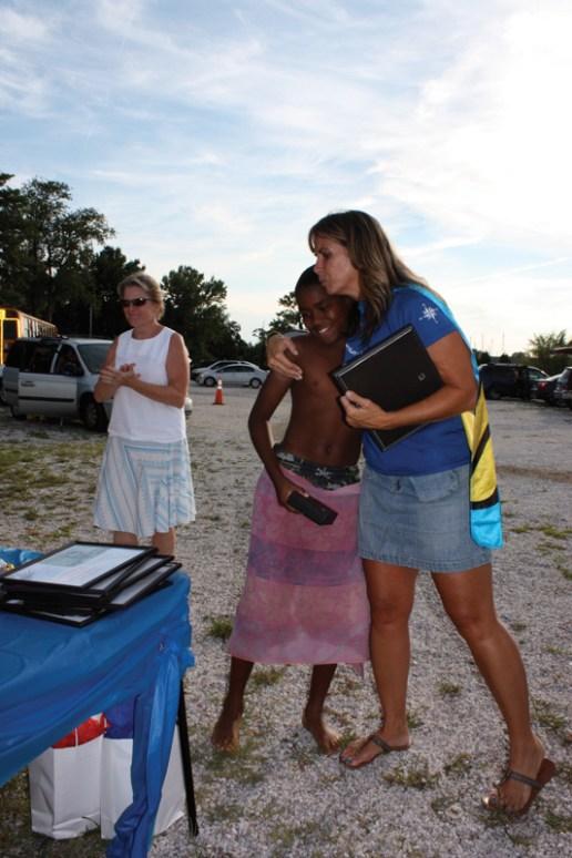Summer Program Director Candi Brown congratulates Sailor of the Year Jodi Downs as Box of Rain founder and Board Chair Anne Harrington looks on.