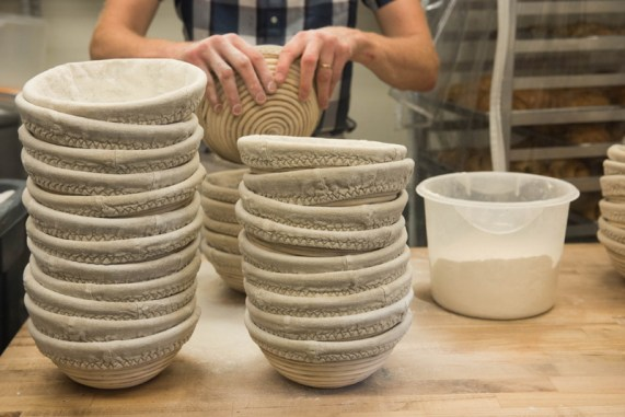 Bakers and Co. owner and baker, Chris Simmons, adds a coat of flour to bannetons (bread proofing baskets) as part of his morning routine at the bakery. Photo by Alison Harbaugh