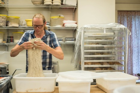 Bakers and Co. owner and baker, Chris Simmons, work with batches of bread dough as part of his morning routine at the bakery. Photo by Alison Harbaugh