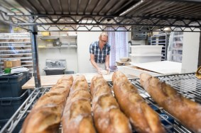 Chris Simmons, owner and baker, prepares bread dough as fresh baguettes cool on the bakery racks early in the morning at Bakers and Co. in Eastport. Photo by Alison Harbaugh