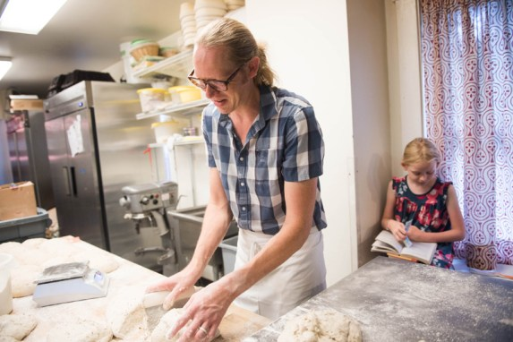 A busy Friday morning at Bakers and Co. in Eastport has owner and baker Chris Simmons preparing bread dough while his oldest daughter Julia reads nearby. Photo by Alison Harbaugh