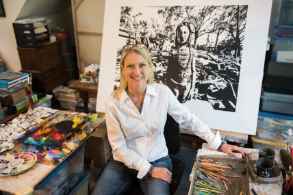 """Photographer & Painter, H.C. Porter in her Annapolis home studio. Behind her is a screen print of her photograph """" Waiting on the Parade """" from her Backyards & Beyond Series that will soon be transformed into a colorful painting. Photos by Alison Harbaugh"""