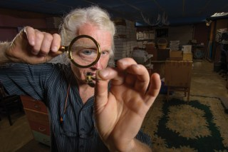 Sam Droege inspecting a bee through a magnifying glass, Patuxent Wildlife Research Refuge, Laurel, MD.